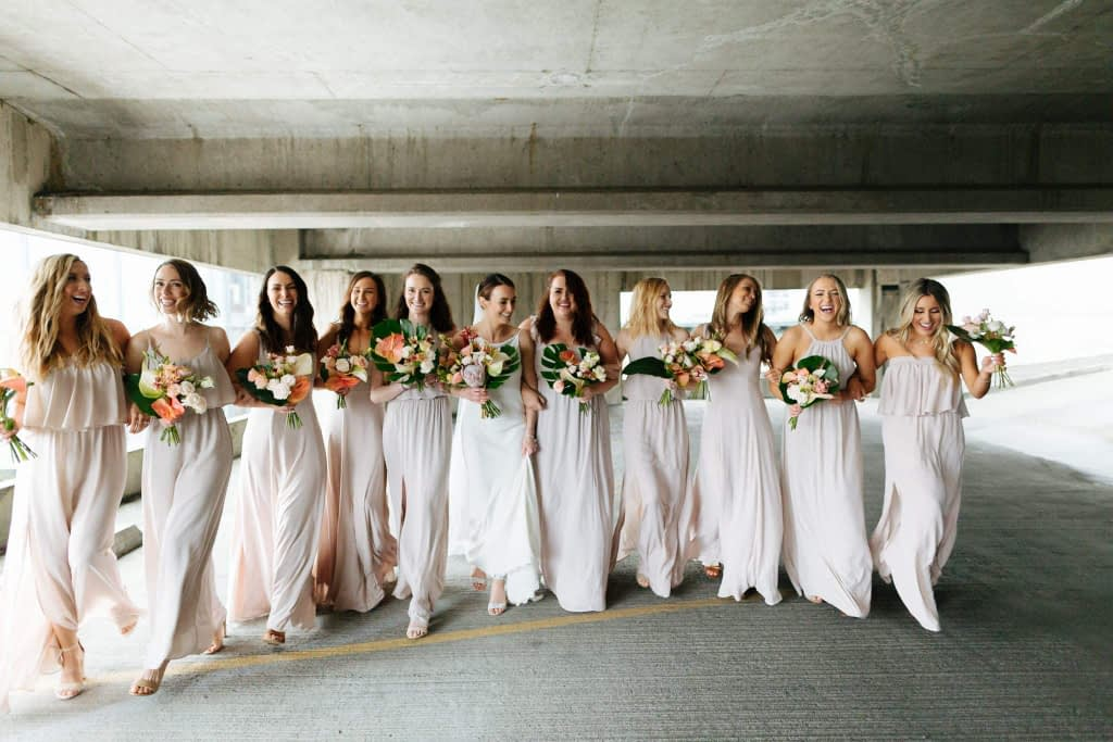 bridesmaids laugh and walk in modern space