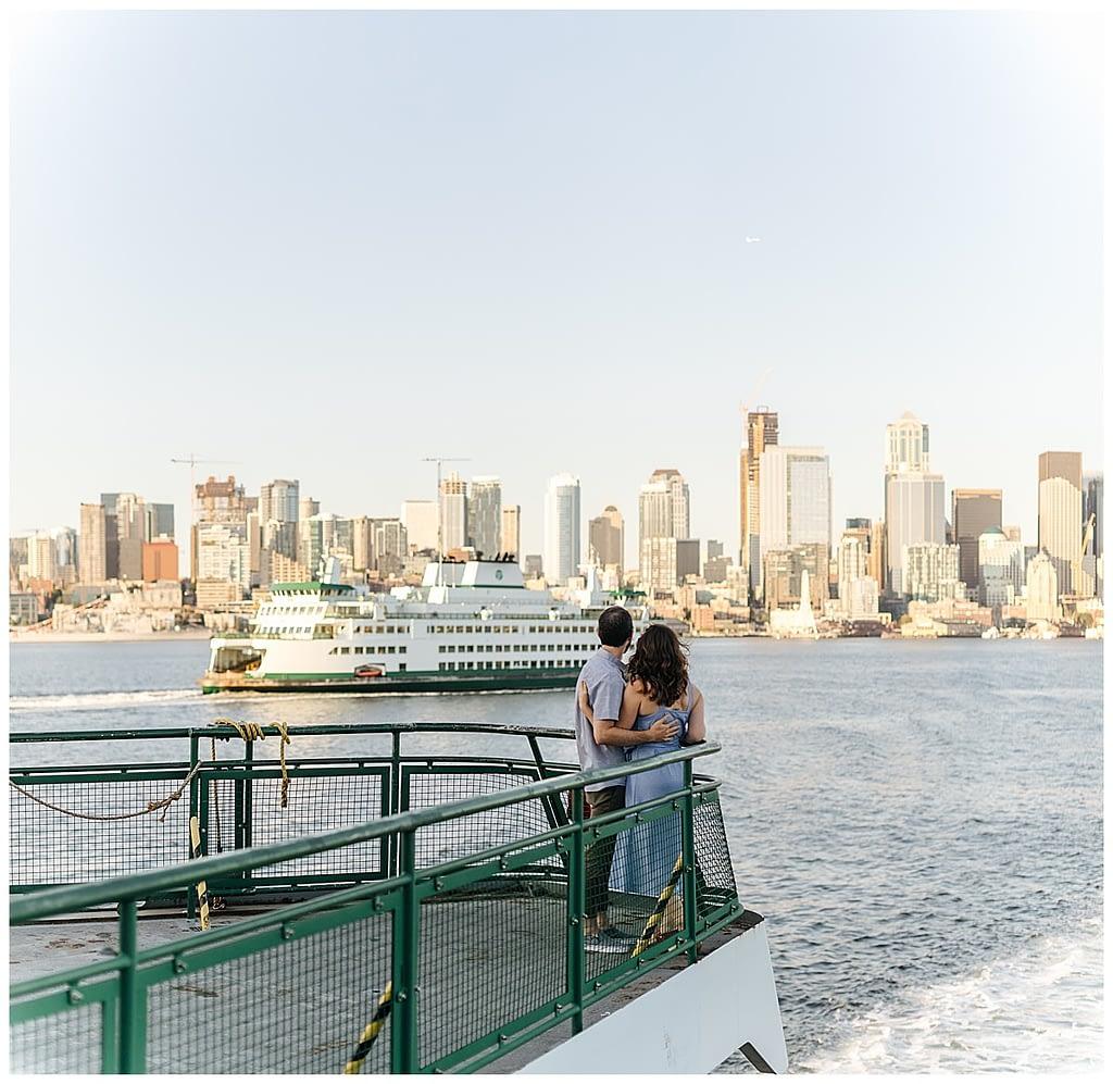 couple looks at seattle skyline Washington State Ferries engagement photos