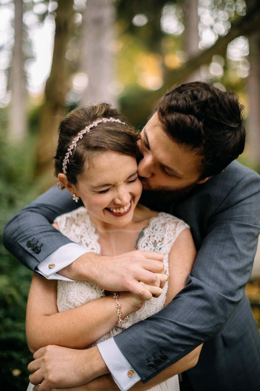 groom kisses bride on cheek volunteer park engagement