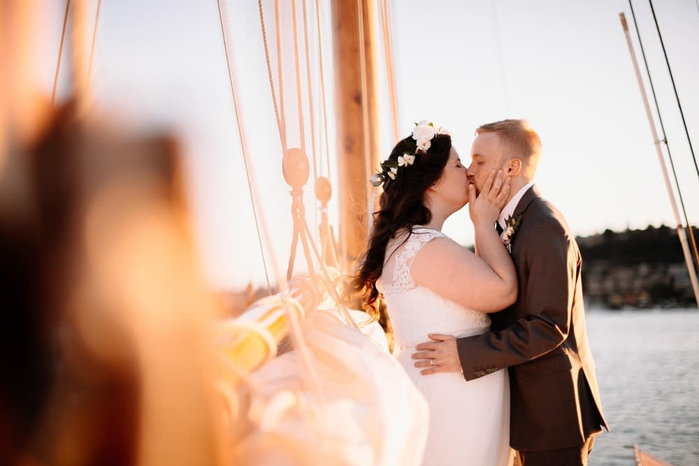 couple kisses on a sailboat lake center for wooden boats wedding