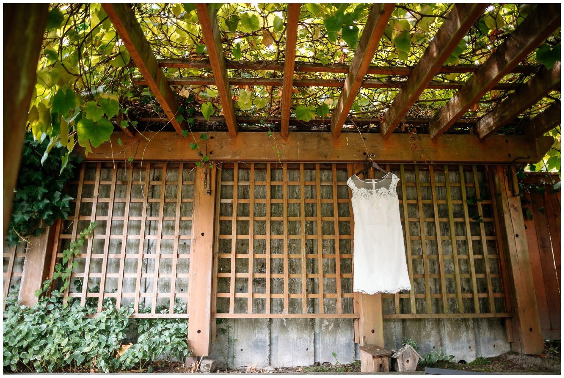 Wedding dress hangs on arch