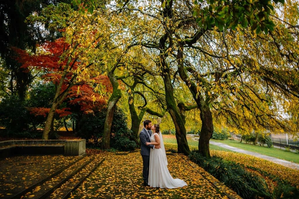 groom and bride kiss under fall leaves