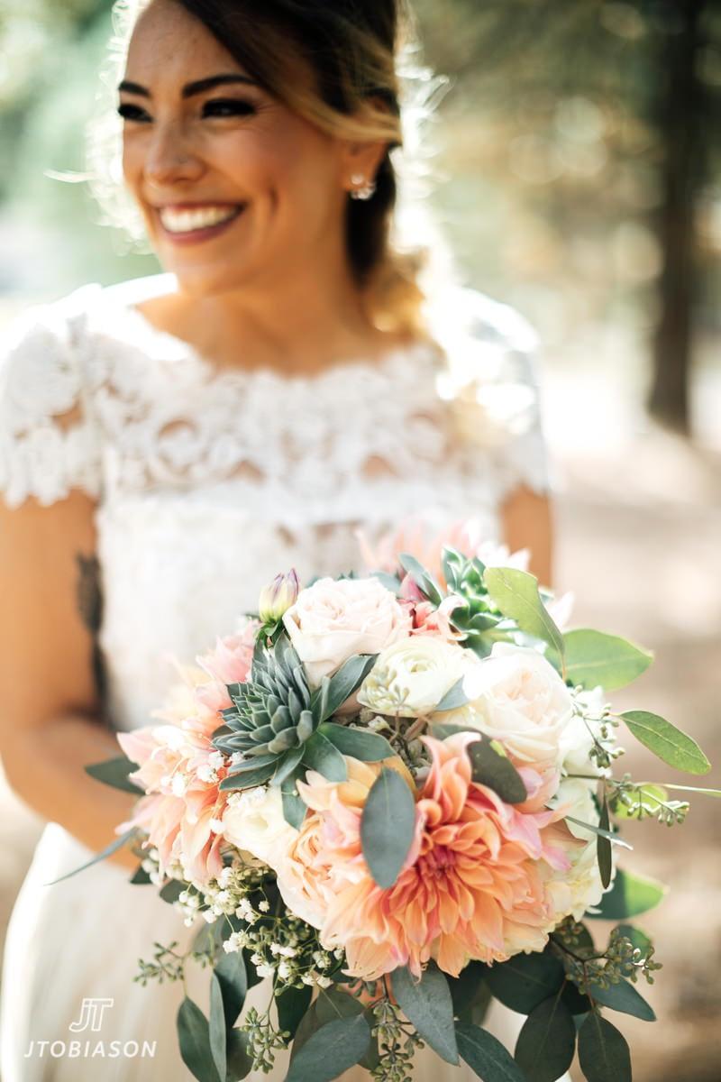 bride smiles with j9bing flower bouquet