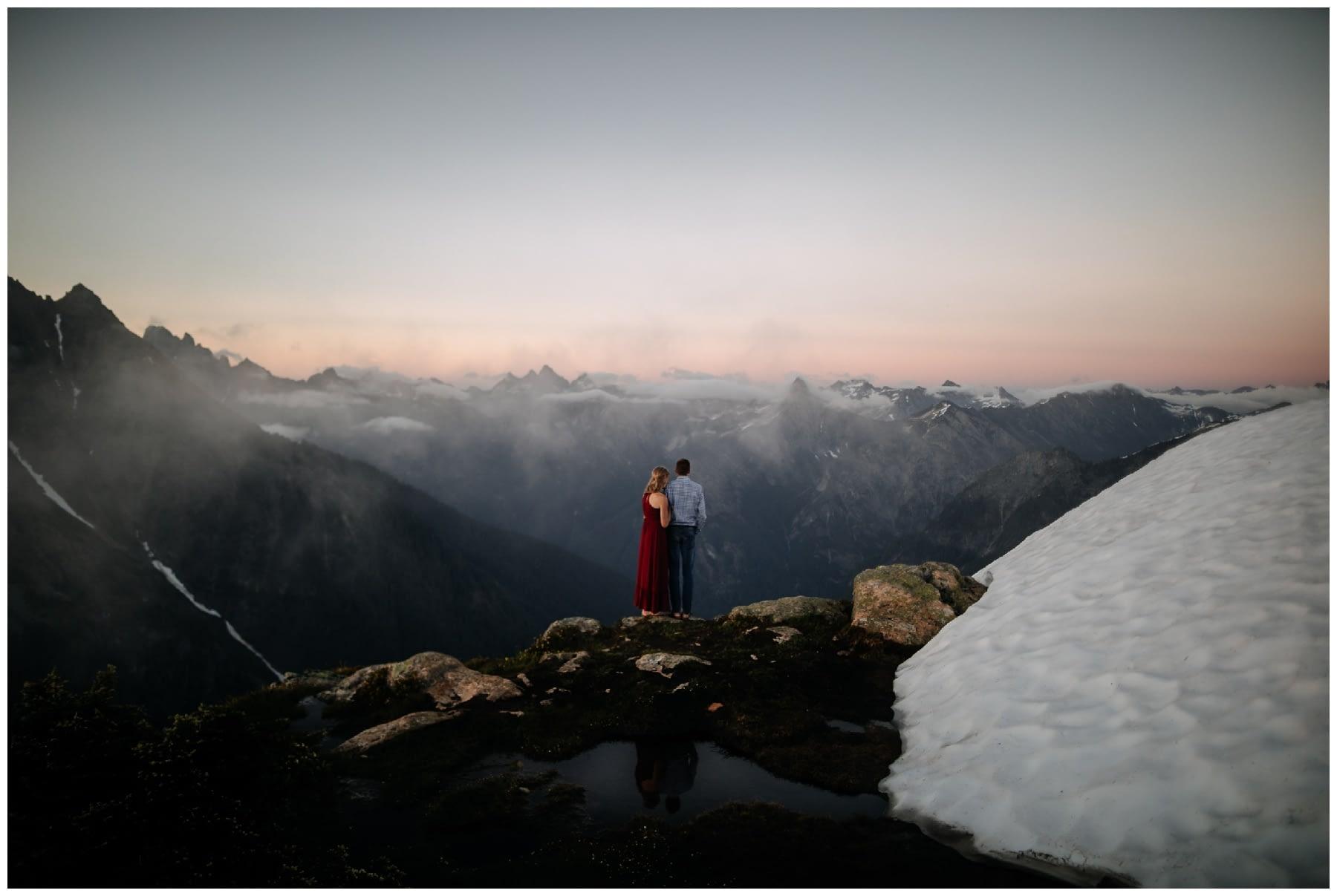 couple kisses during cascade mountaintop sunset engagement