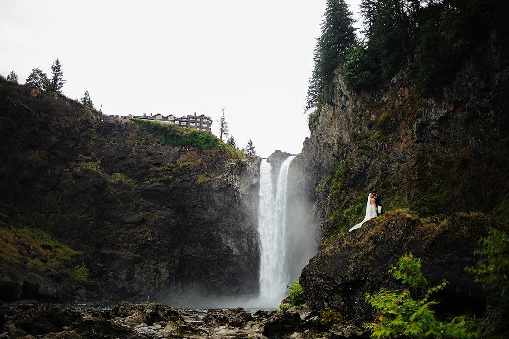 Bride and groom kiss beneath snoqualmie falls Salish Lodge weddi