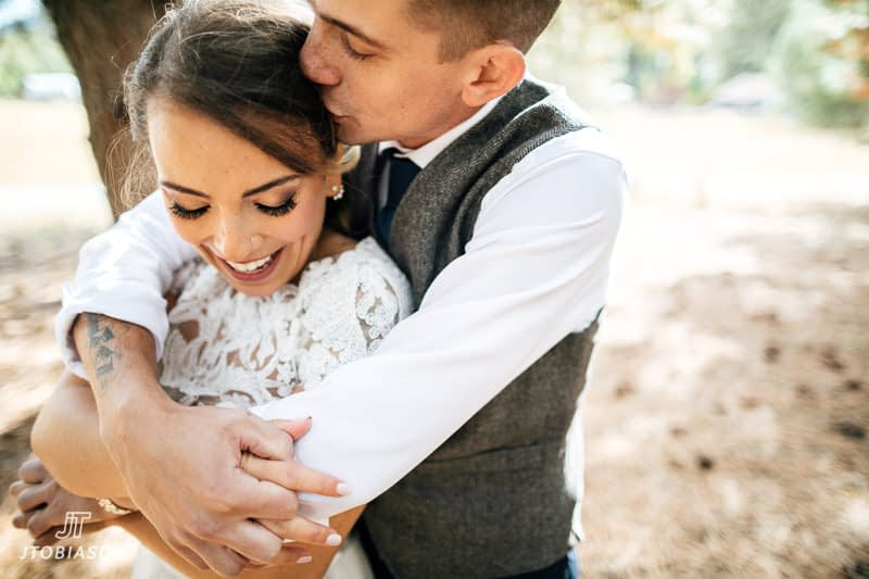 groom kisses bride brown family homestead wedding