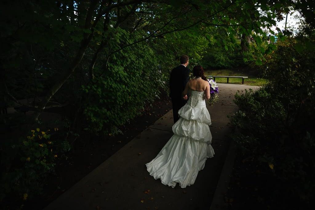 Bride and groom walk through the woods Salish Lodge wedding venu