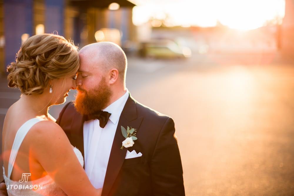 Bride and groom kiss in sunset westland distillery wedding