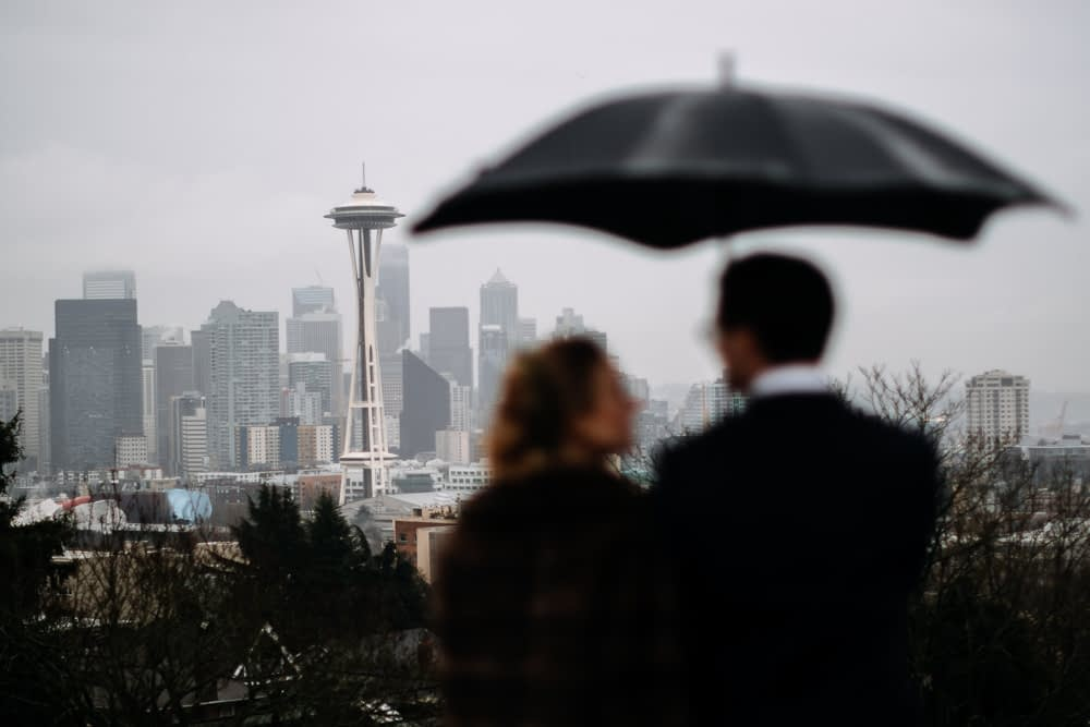 bride and groom look at downtown Seattle under umbrella