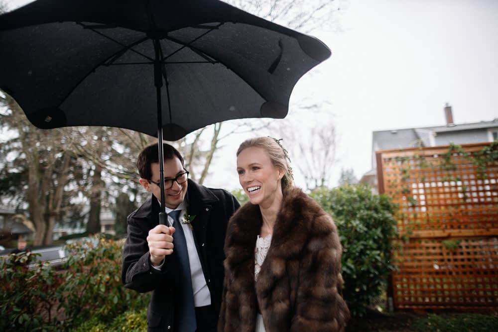 groom holds umbrella for bride