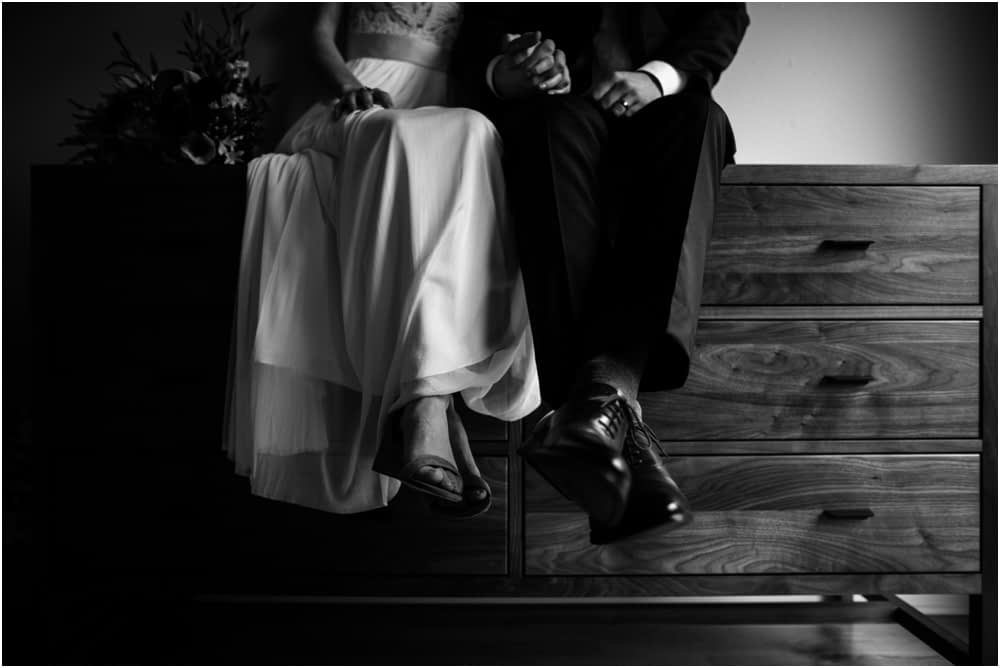 couple sits on dresser in wedding clothes