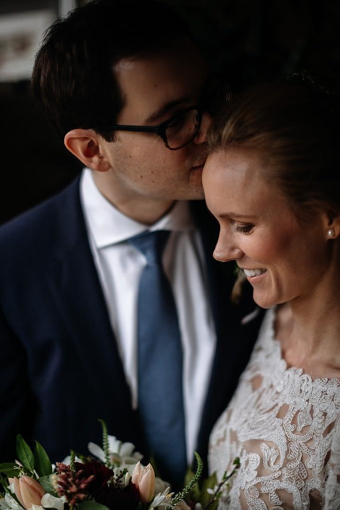 groom kisses bride on her head