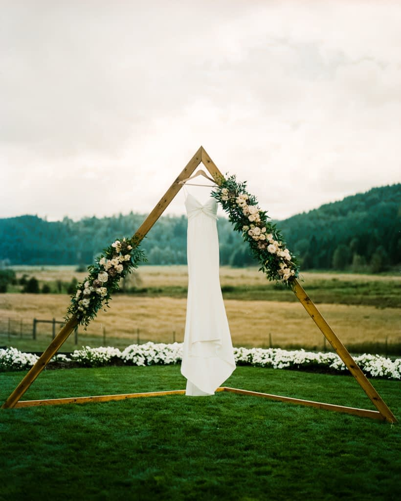 wedding dress hangs on an arch film photo