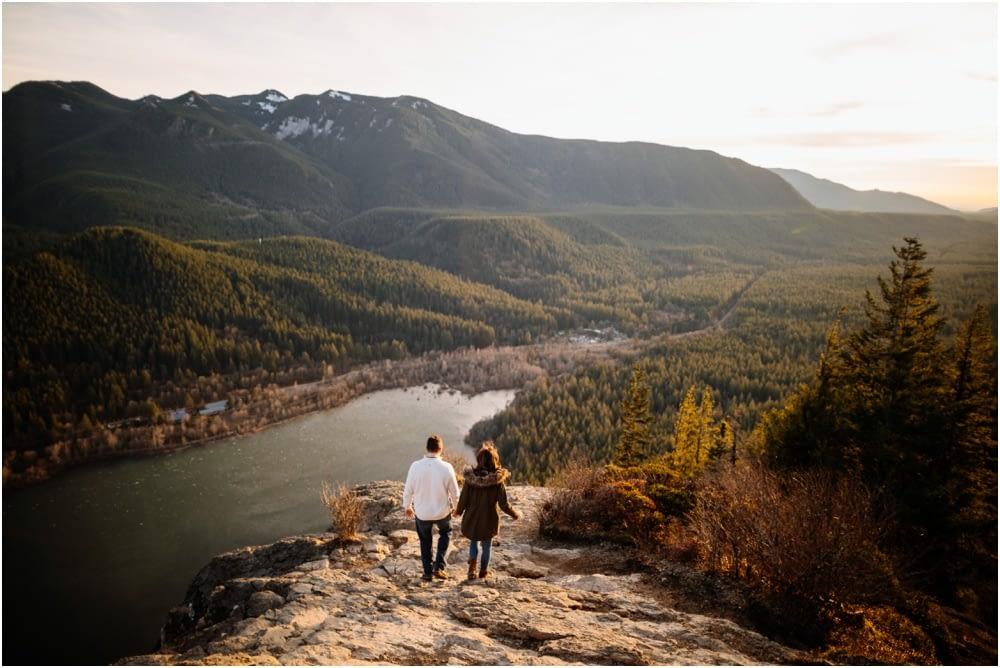 Couple walks down hill of rocks Sunset Rattlesnake Ledge Engagement