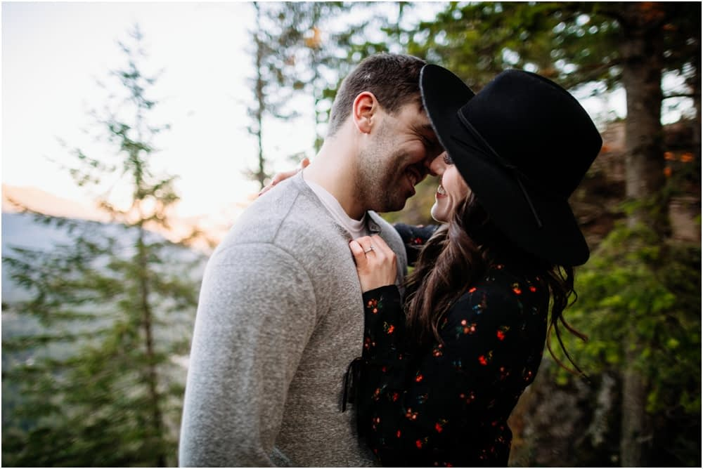 couple stands in the trees and smiles Rattlesnake Ledge Engagement