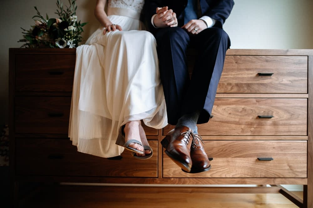 bride and groom sit on dresser downtown seattle elopement