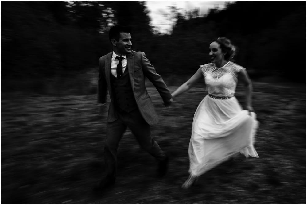groom and bride run at dusk Preston Community Center wedding
