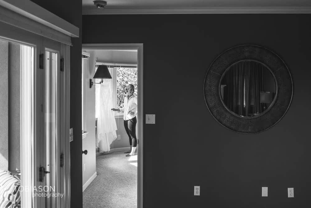 3 - bride looks at her dress in the window photo