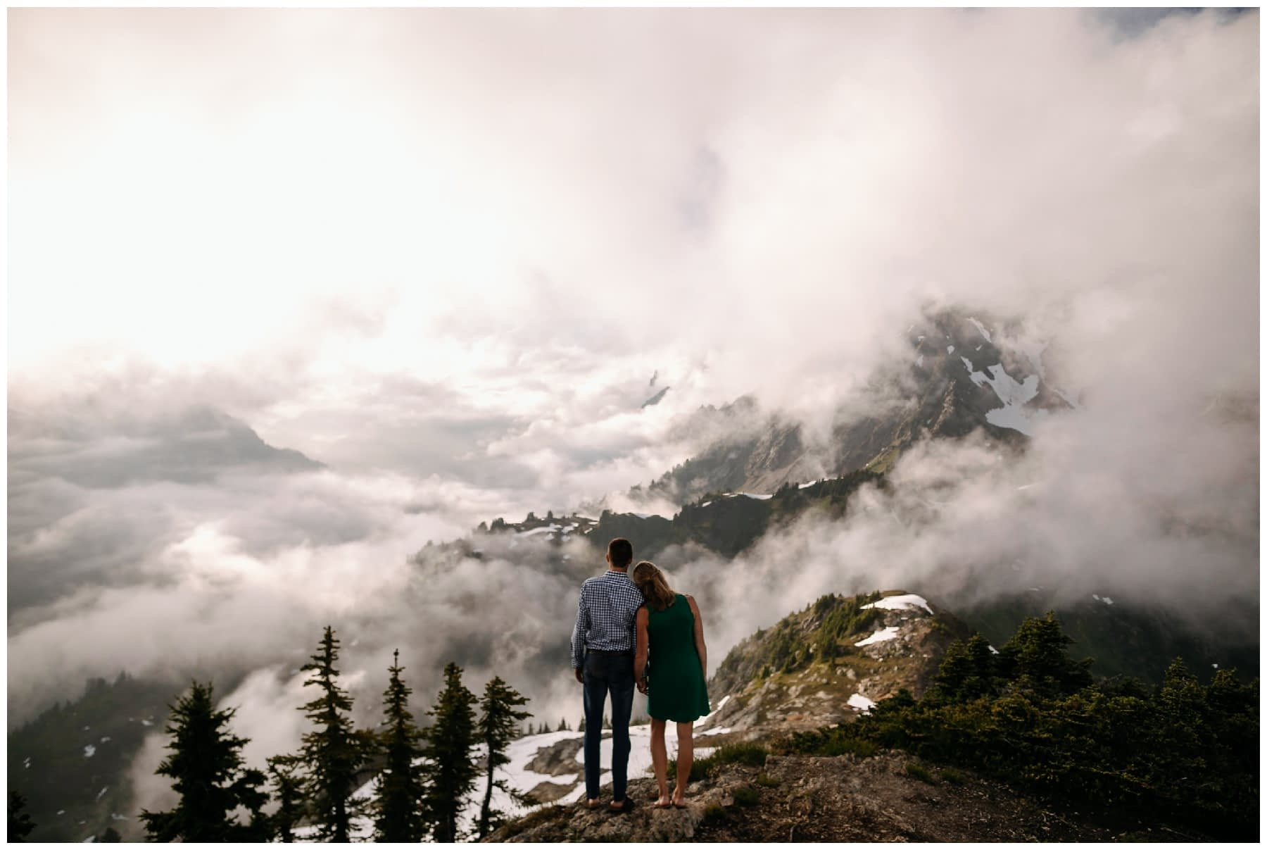 couple looks out over clouds sunset backpacking engagement