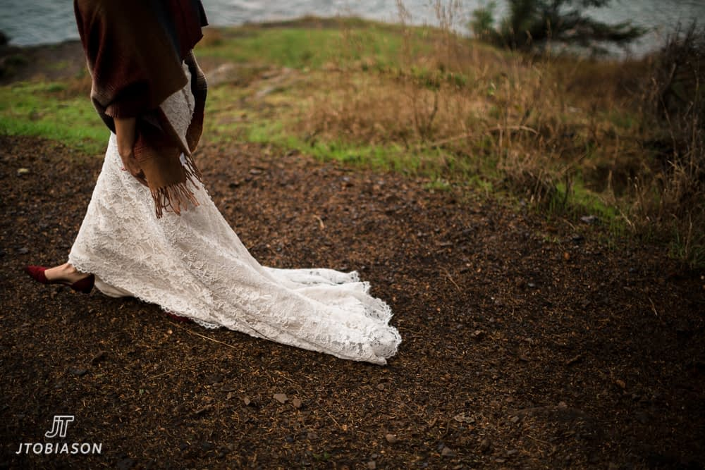 Bride walks across dirt with red shoes