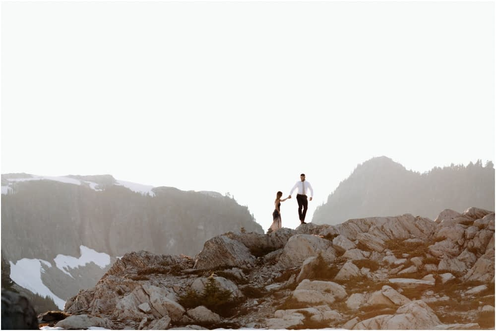 bride and groom walk along rocks Artist Point hiking engagement