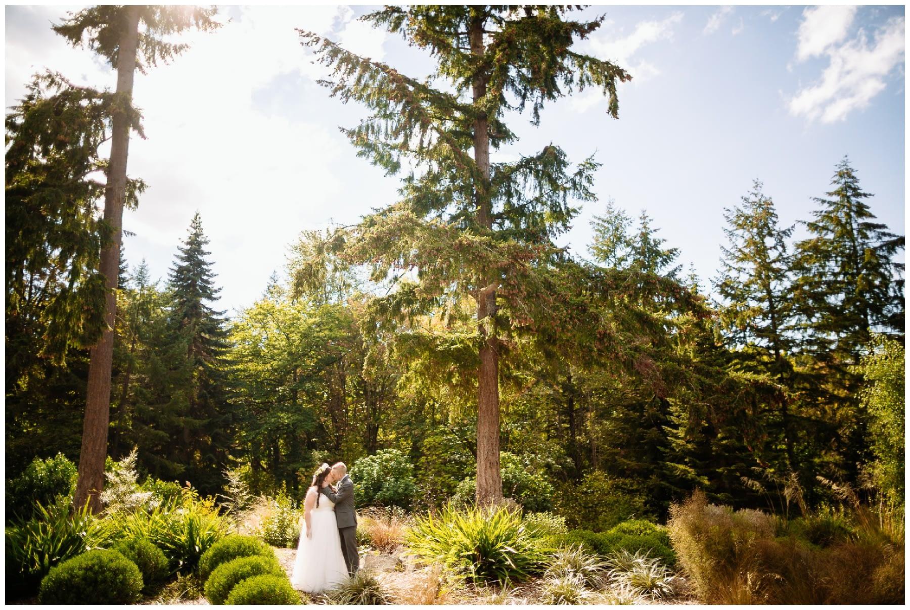 bride and groom stand in susnet washington park arboretum wedding