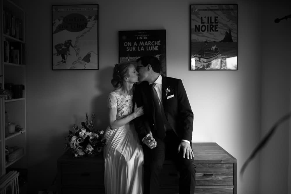 bride and groom sit on dresser and kiss in black and white