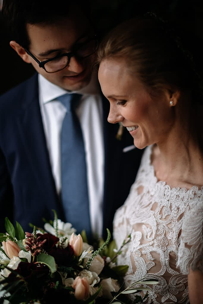 Bride and groom smile holding bouquet