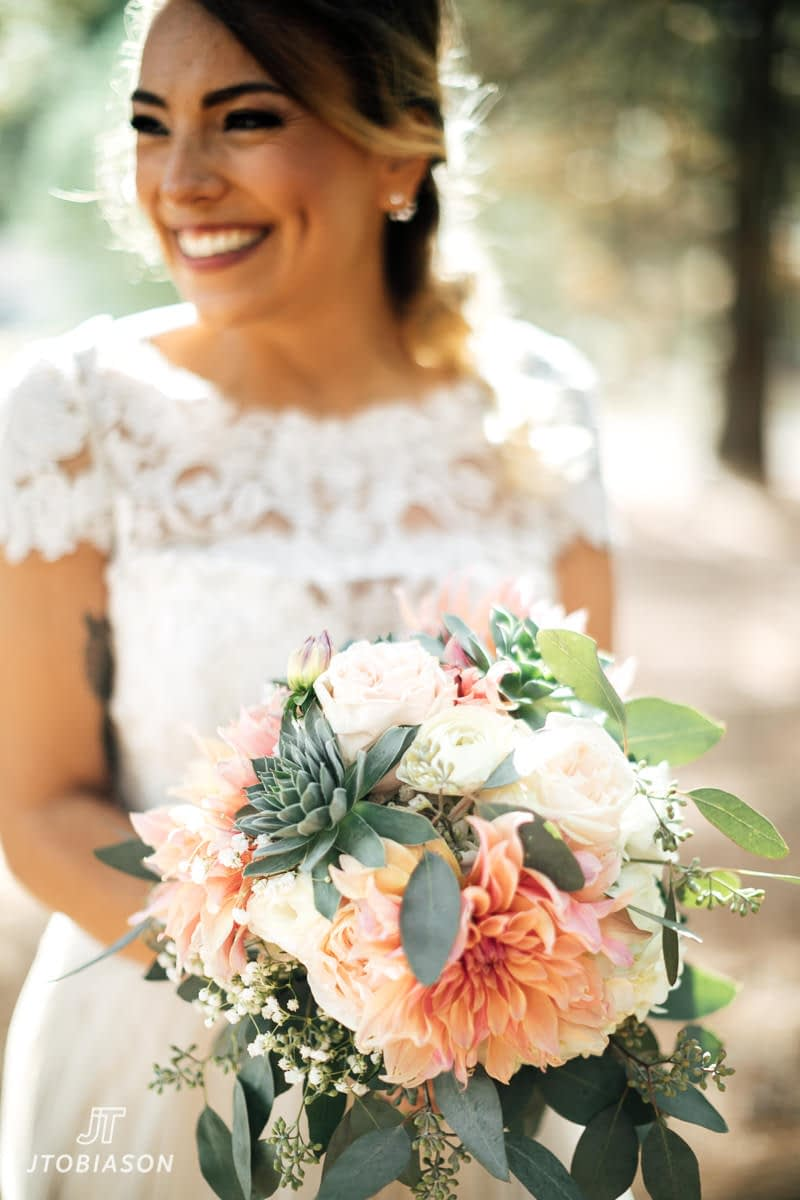 bride smiles with j9bing flower bouquet