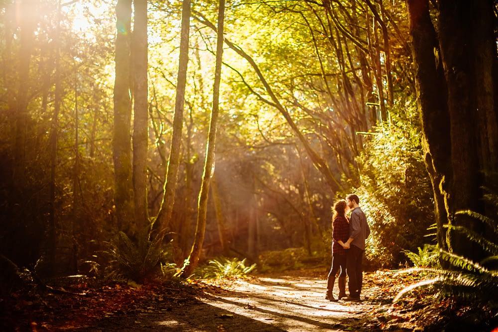 couple kisses in sunrise light discovery park engagement