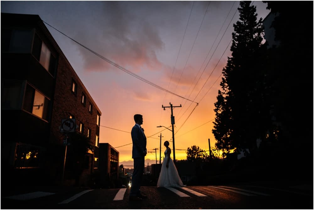 bride and groom stand in sunset ranier chapter house wedding