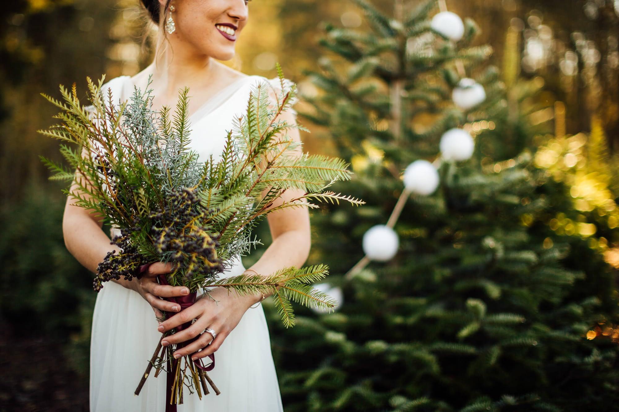 bride smiles holding bouquet trinity tree farm wedding