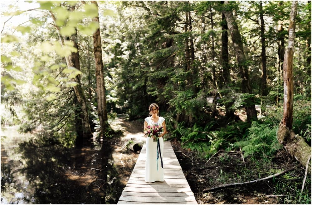 bride stands on bridge PNW camping wedding