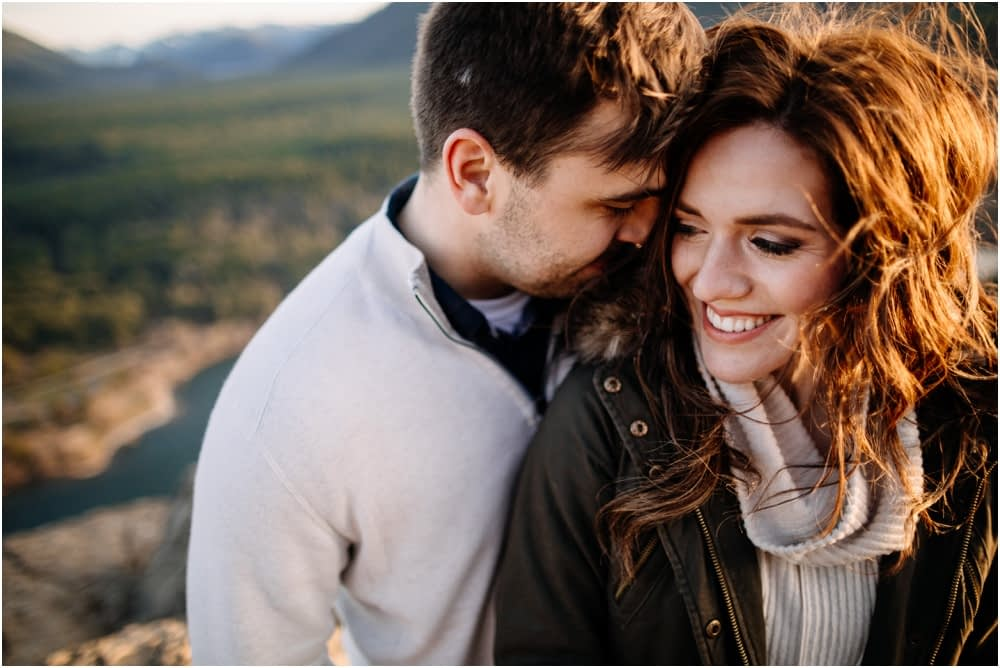 Man kisses woman's cheek hiking engagement