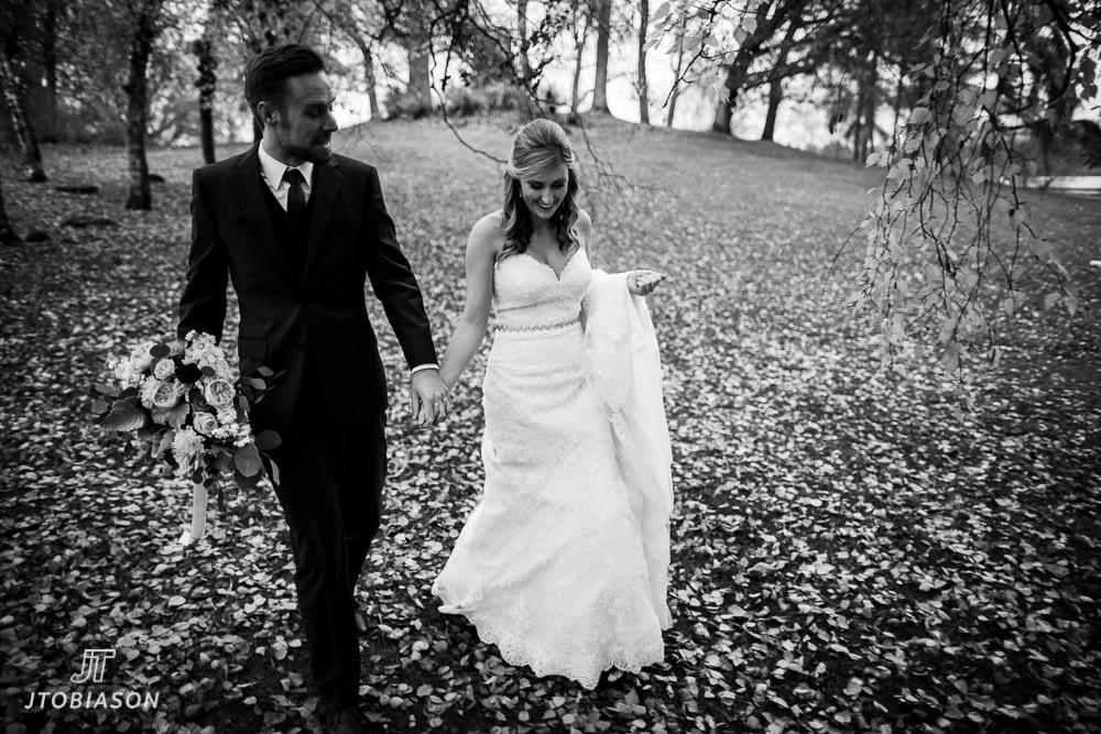 couple walks through fall leaves great hall at green lake wedding photo