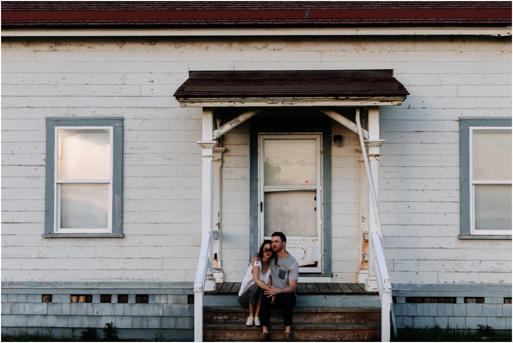 couple sits on porch of old house Sunset Discovery Park Engagement