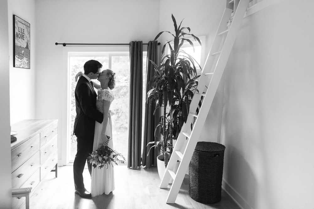 bride and groom kiss in home black and white